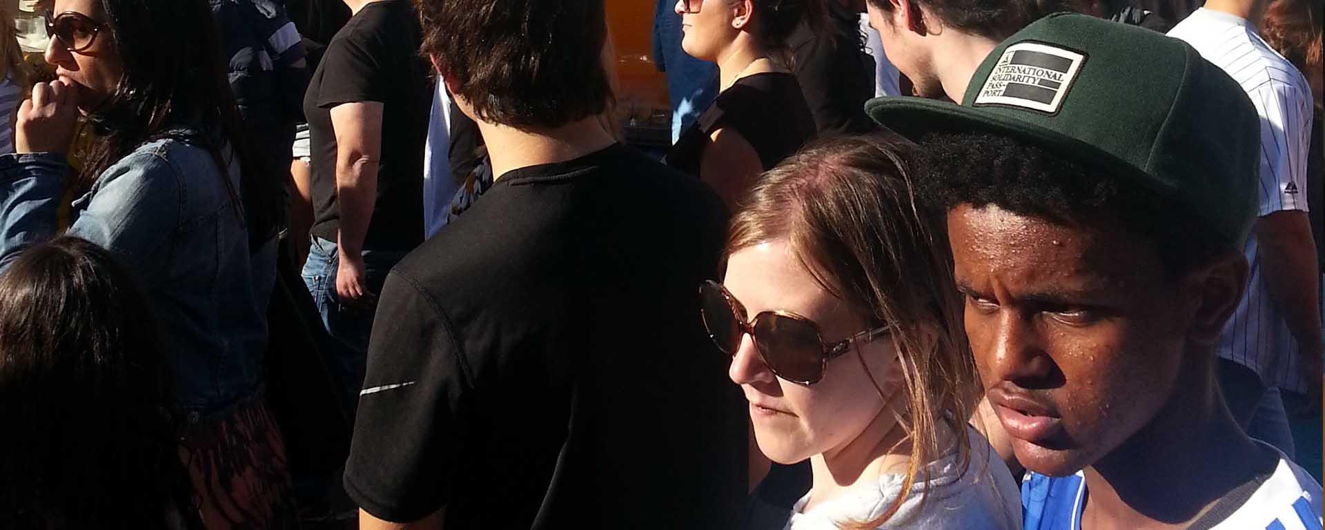 A Black boy and White woman walk through a crowd