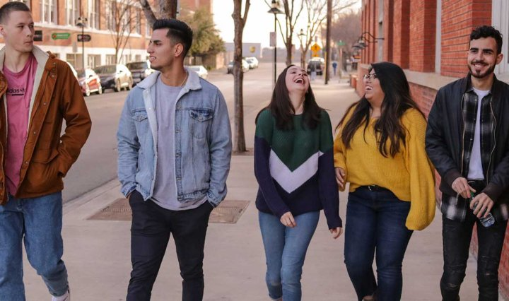 Three young men and two young women talk and laugh as they walk the street