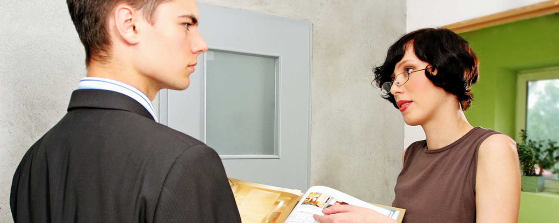 A white man frowns as a white woman is talking to him and pointing to a book