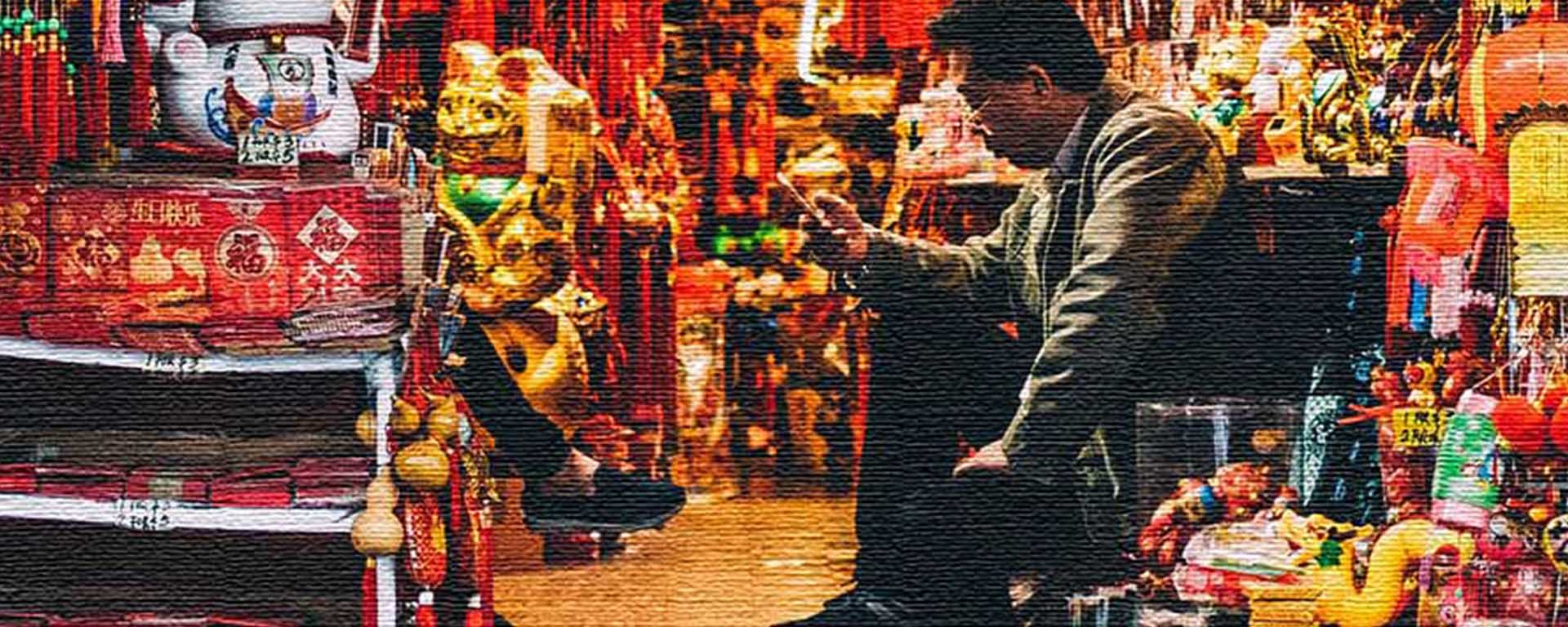 A Chinese man sits in a Chinese shop reading his phone