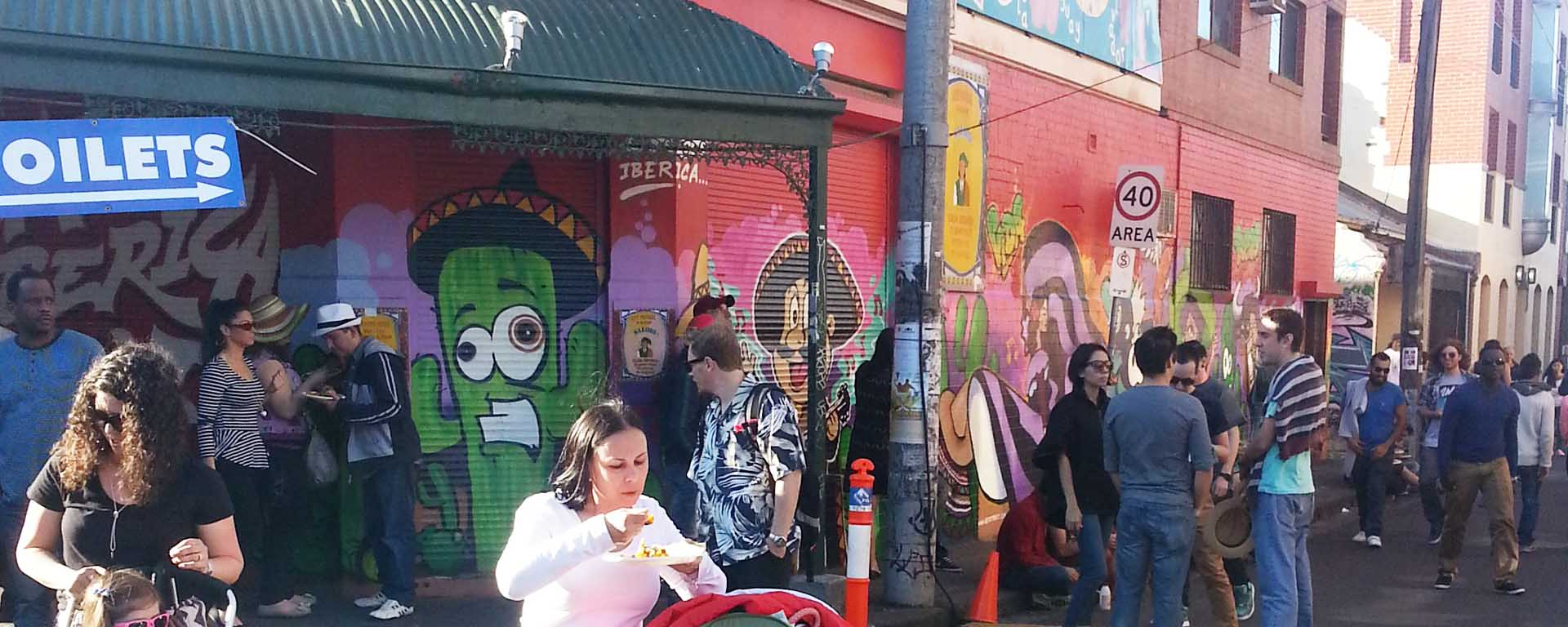 People eat food and chat on Johnston Street during the Hispanic Latin American Festival, Melbourne