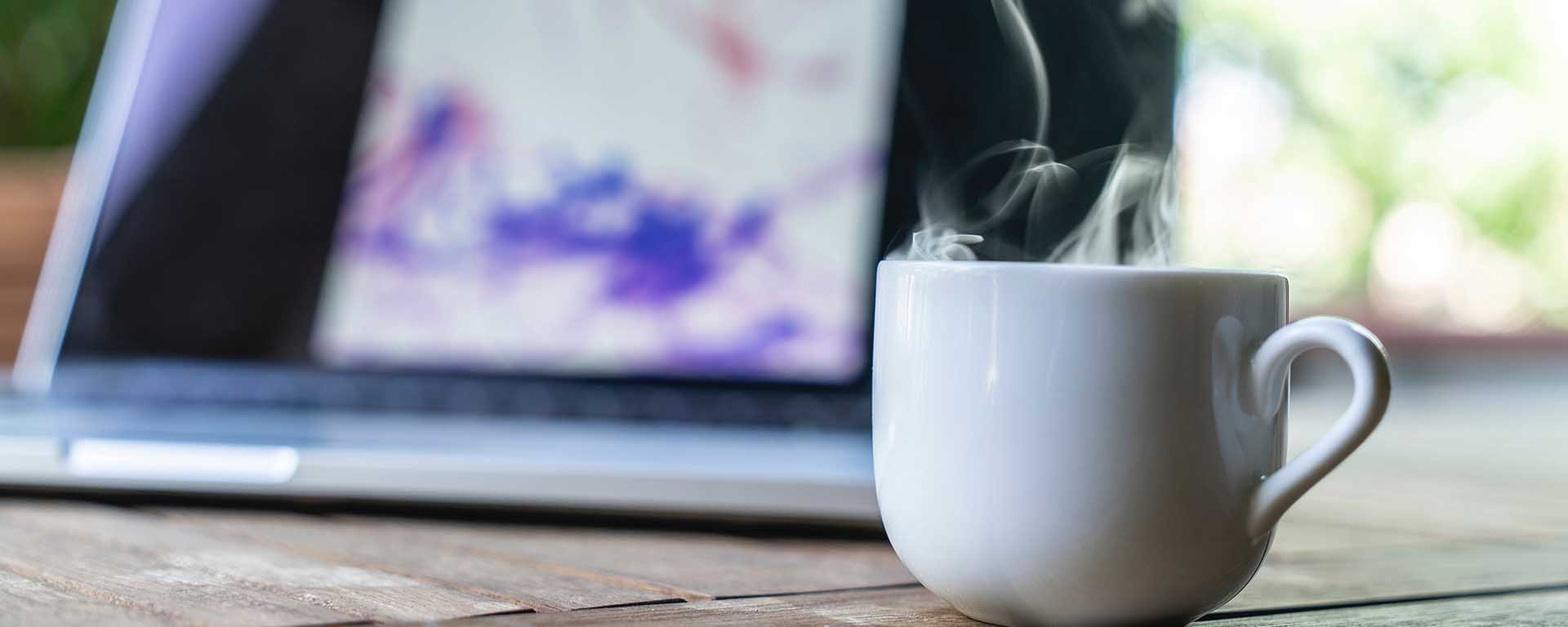 White mug with steam. A laptop in the background