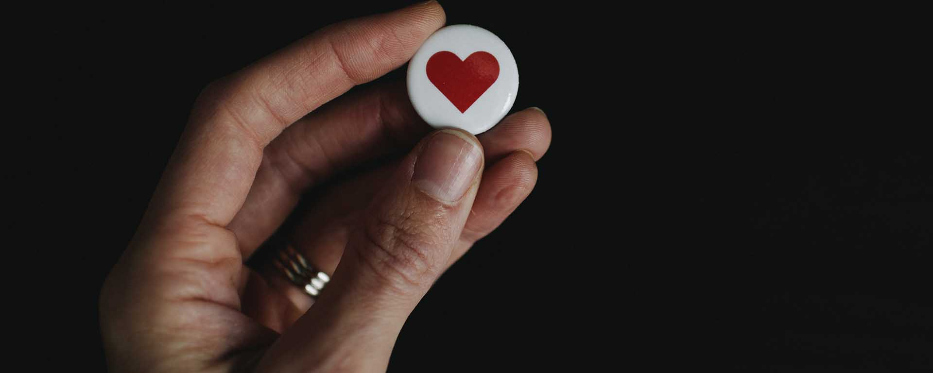 A hand holds up a white badge with a red love heart