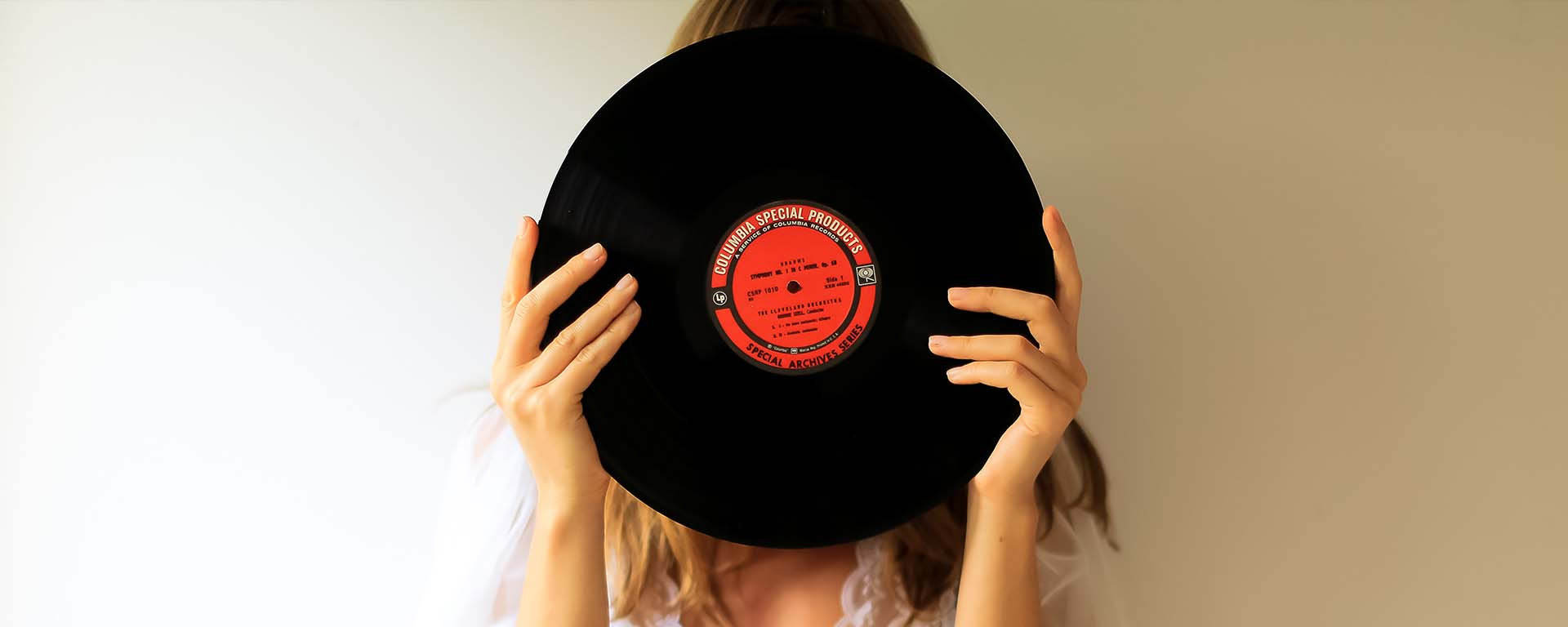 A white woman holds up a record over her face