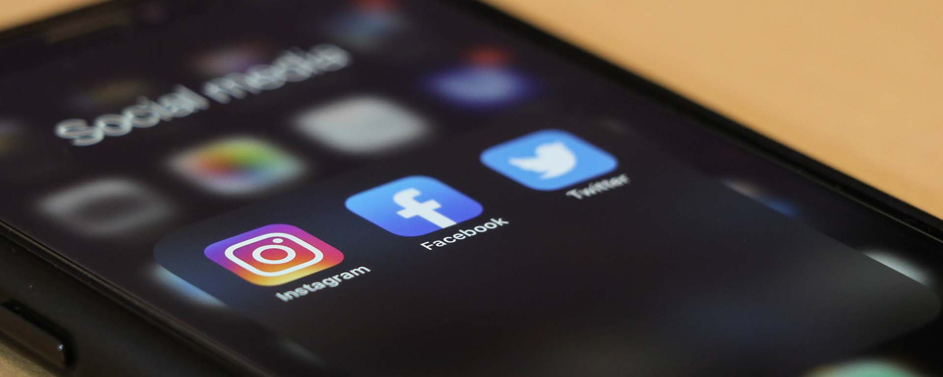 A mobile phone with Instagram, Facebook and Twitter apps showing on the homepage