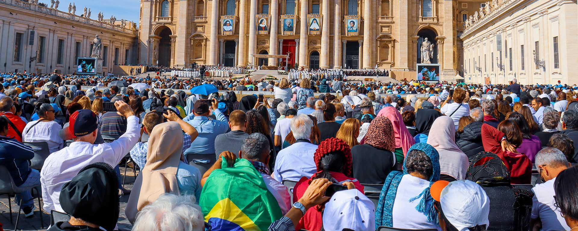A large crowd of Catholic people pray and hold one another's shoulders