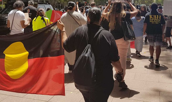 Protesters march through Sydney. Two people hold a large Aboriginal flag as they walk