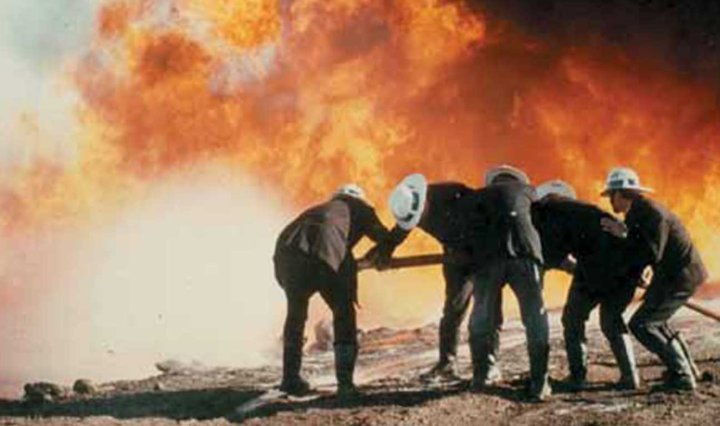 Firefighters bent over a hose, while a large blaze burns behind them, along with a huge wall of black smoke