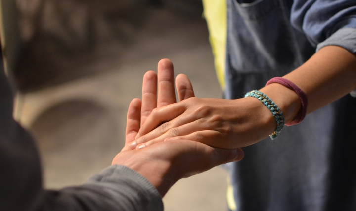 Close up of two people with outstretched hands touching