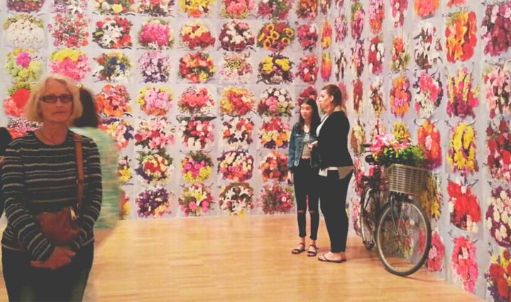 People stand for photos in front of Ai Weiwei's art, 600 Days of Flowers