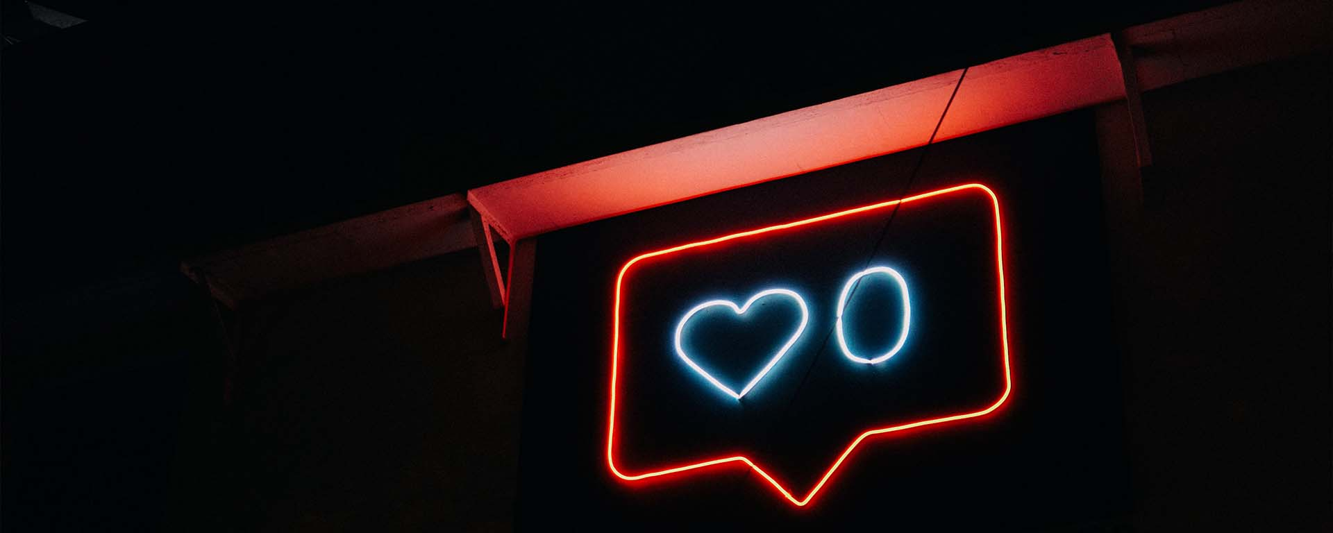 Neon sign showing a speech bubble sign with a love heart and the number zero