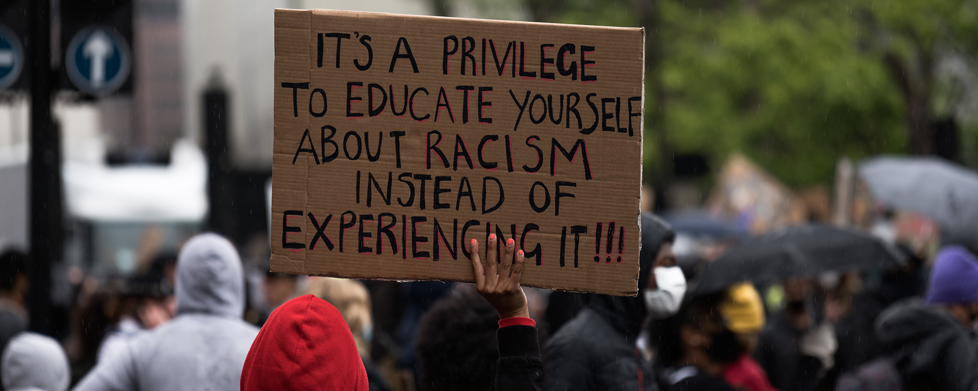 A Black person is seen from behind at a protest, holding a sign. It reads: it's a privilege to educate yourself about racism instead of experiencing it