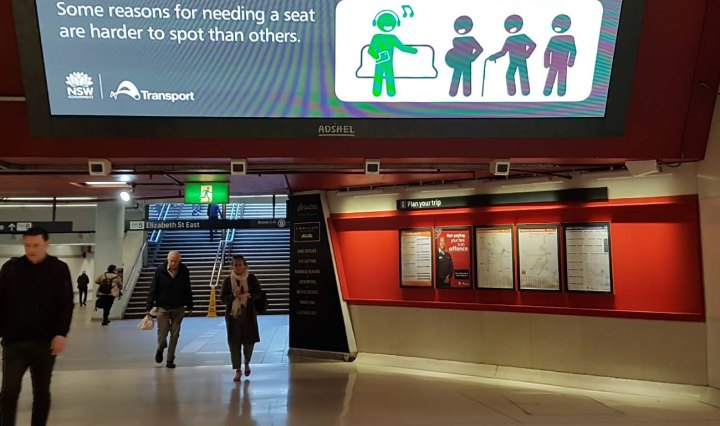People walking in Martin Place station underground. A large monitor shows an ad with stick figure people: one is green, seated, and listening and singing to their music; the other figures are black - one is pregnant, the other uses a walking stick, and the other stands
