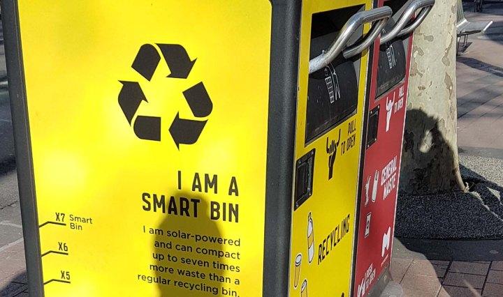 Yellow smart bin in Melbourne. Writing on the side says 'I am a smart bin'
