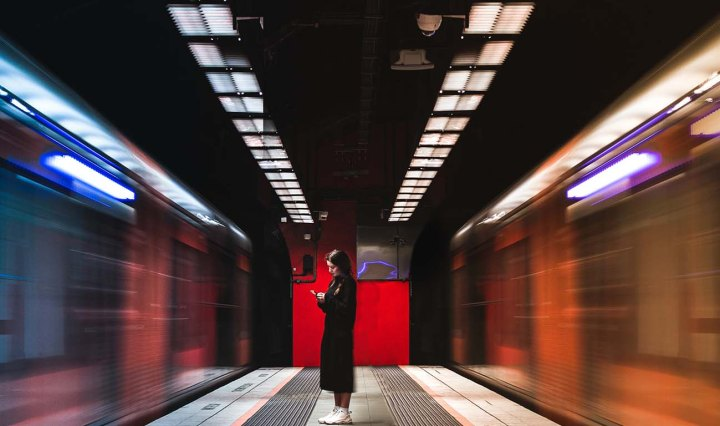 Woman standing in Sydney train station looking at her phone as blurred trains rush past on either side