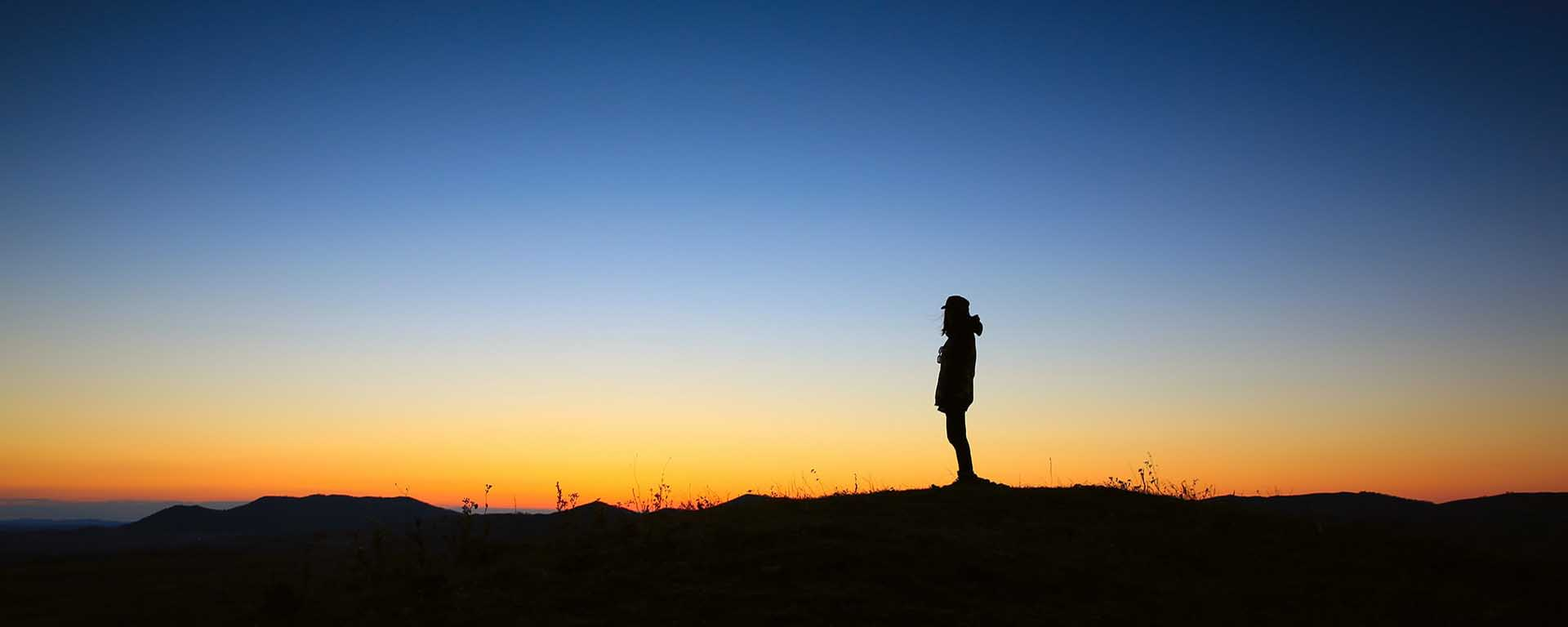 A person stands in the far horizon at dusk