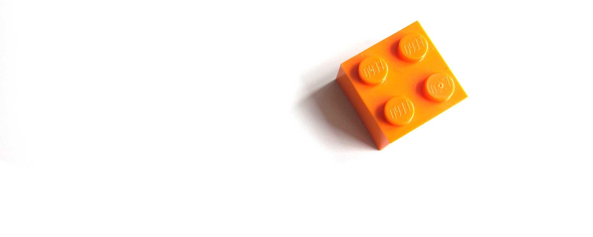 Orange lego block against a white background