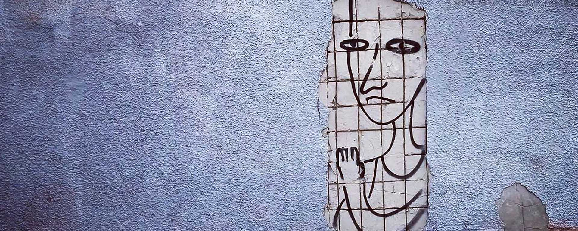 A textured wall with a poster drawing of a person behind a grid
