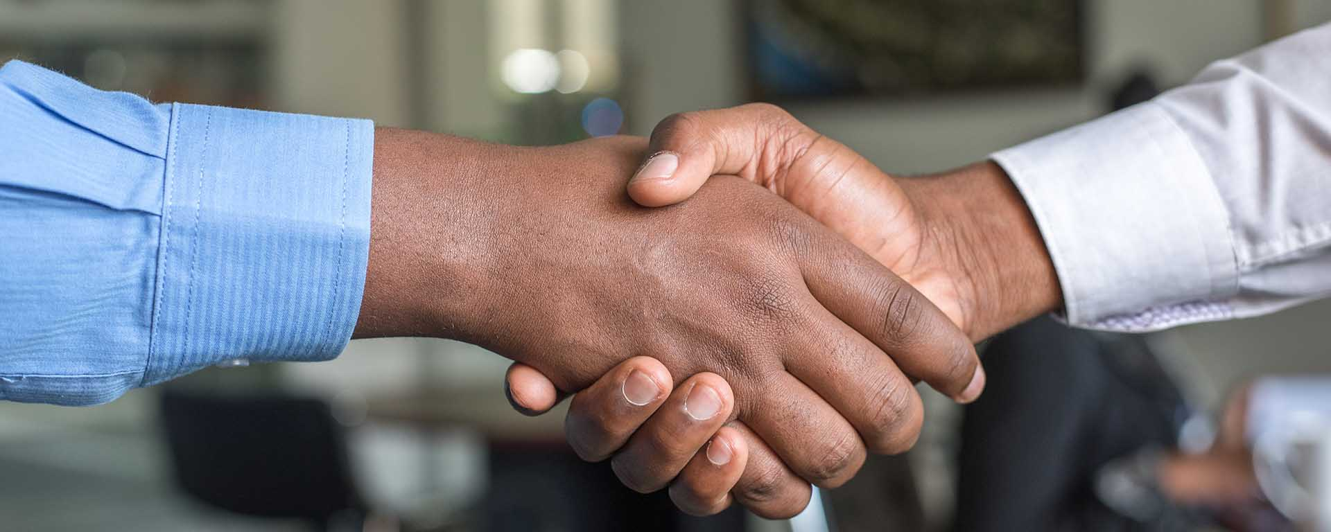 Close up of shaking hands of a Black and Brown man