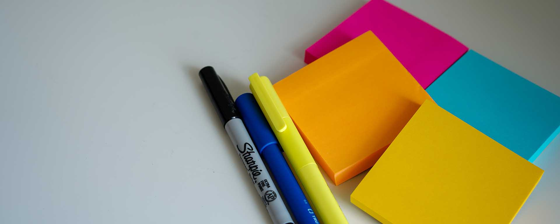 Colourful sticky notes, a Sharpie and highlighters on a blank table