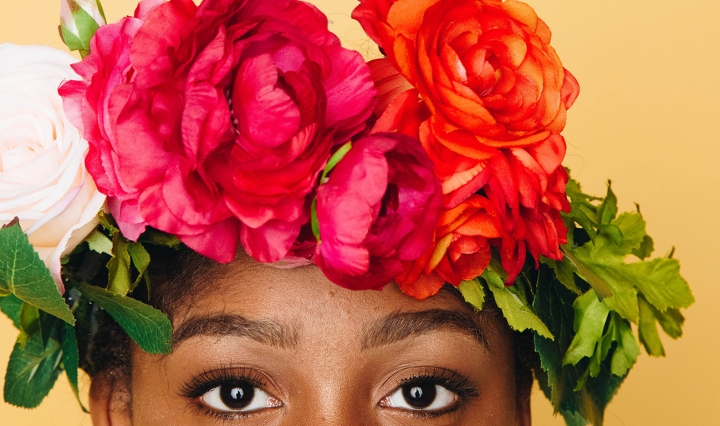 The top of a Black woman's face. She wears a crown of bright flowers