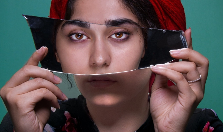 A Brown South Asian woman holds up a piece of broken mirror over her face that shows her reflection