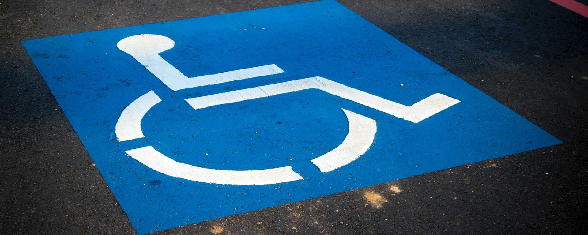 Disability parking sign on the road, showing a picture of a wheelchair