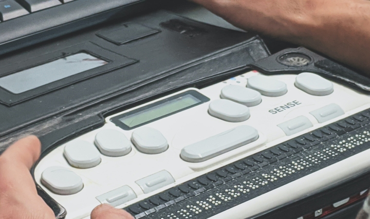 A white man's hands are seen over a braille keyboard