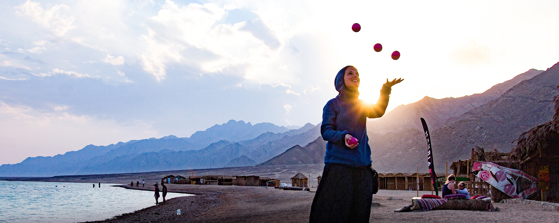 A girl if juggling on a beach wearing a hoodie
