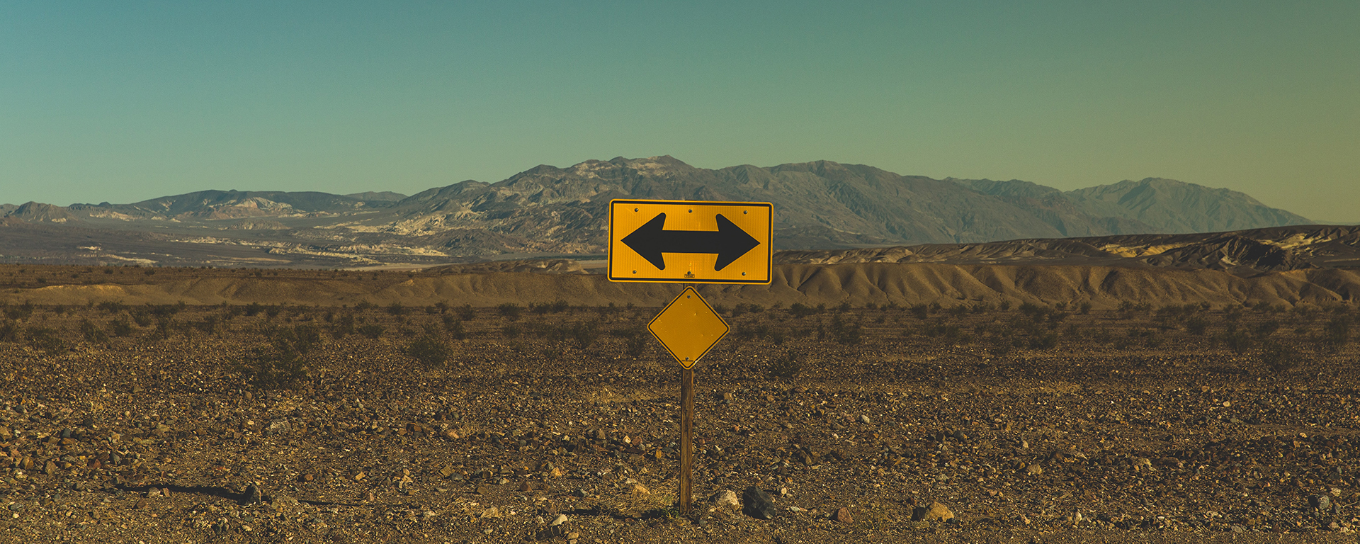 Road sign showing arrows in opposite directions