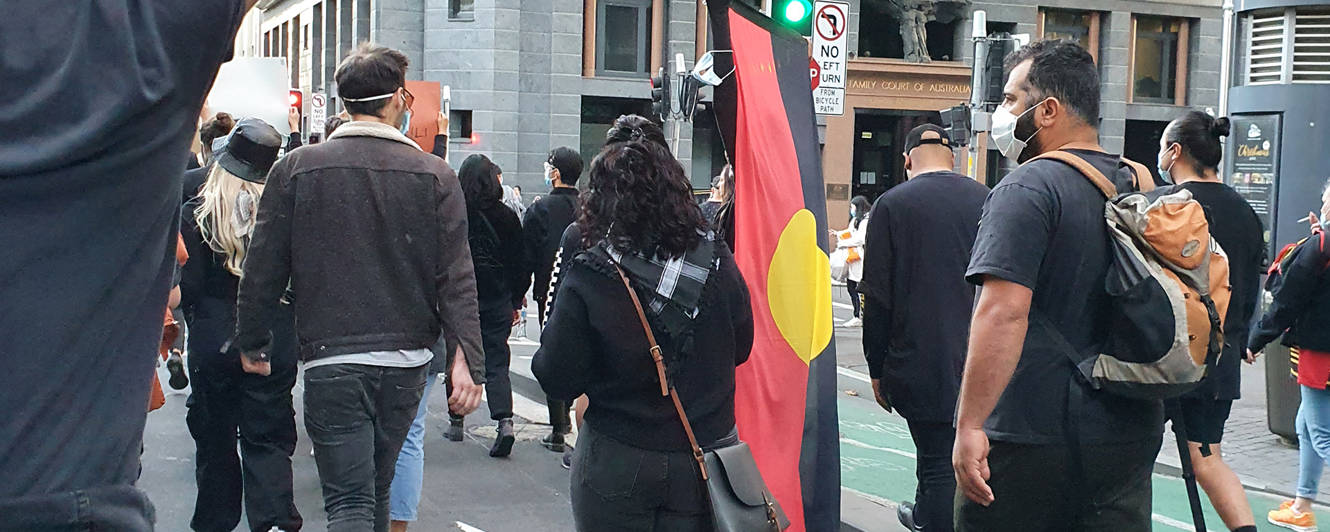 Protesters at the Stop Black Deaths in Custody march in Sydney. One man carries the Aboriginal flag