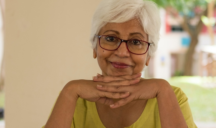 Older South Asian woman with dark skin wears glasses and smiles with her hands folded