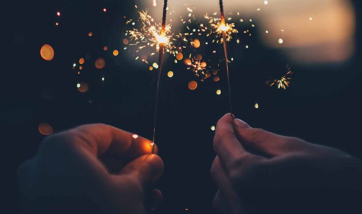 Two white hands hold us sparklers in the darkness