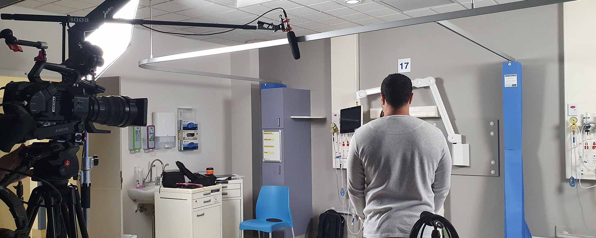 Man stands with his back to the audience, in the middle of a hospital room. A large camera is on the left hand side