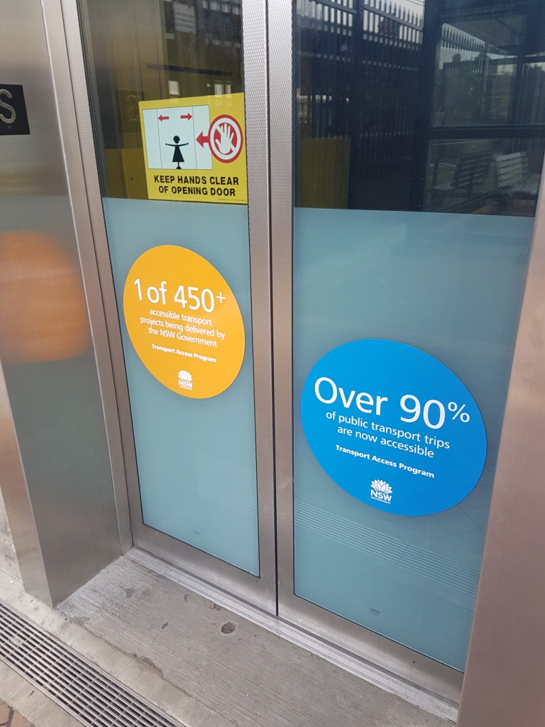 lift with 2 large stickers. One says 'One of 450+ accessible transport projects…' the other says 'Over 90% of public transport trips are now accessible'