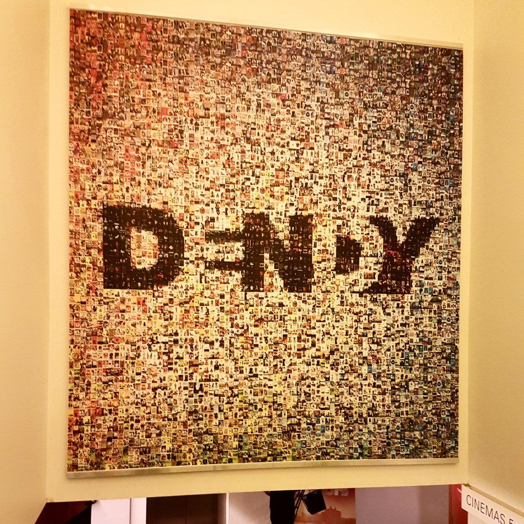 Poster showing Dendy logo, with hundreds of tiny polaroids in the background