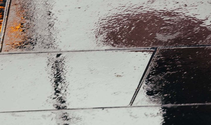 Reflection on a rainy footpath, of a person standing with an umbrella