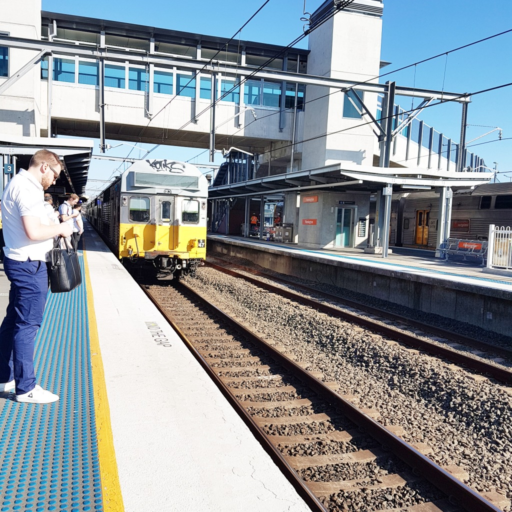 People stand at the edge of a train station platform on a bright sunny day
