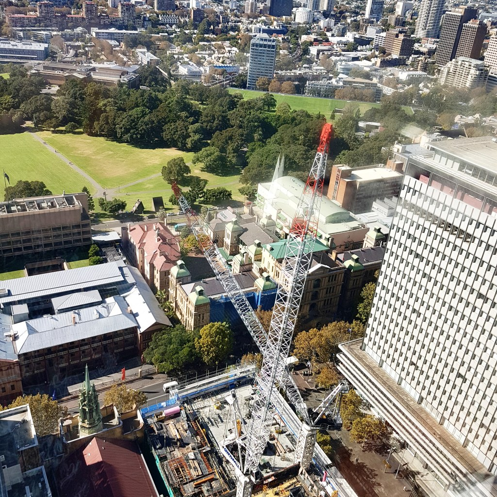 Aerial view of Sydney CBD showing a large crane, a large park, and tall buildings in the background