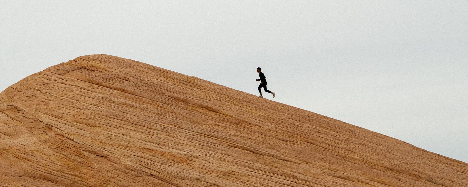 A person runs up a steep mountain