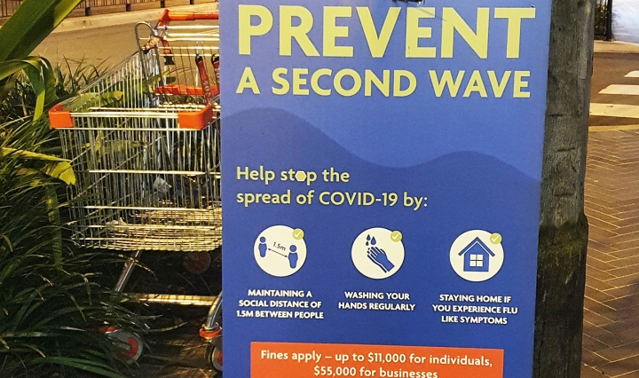Street sign says 'Prevent aa second wave.' Next to is an abandoned shopping trolley