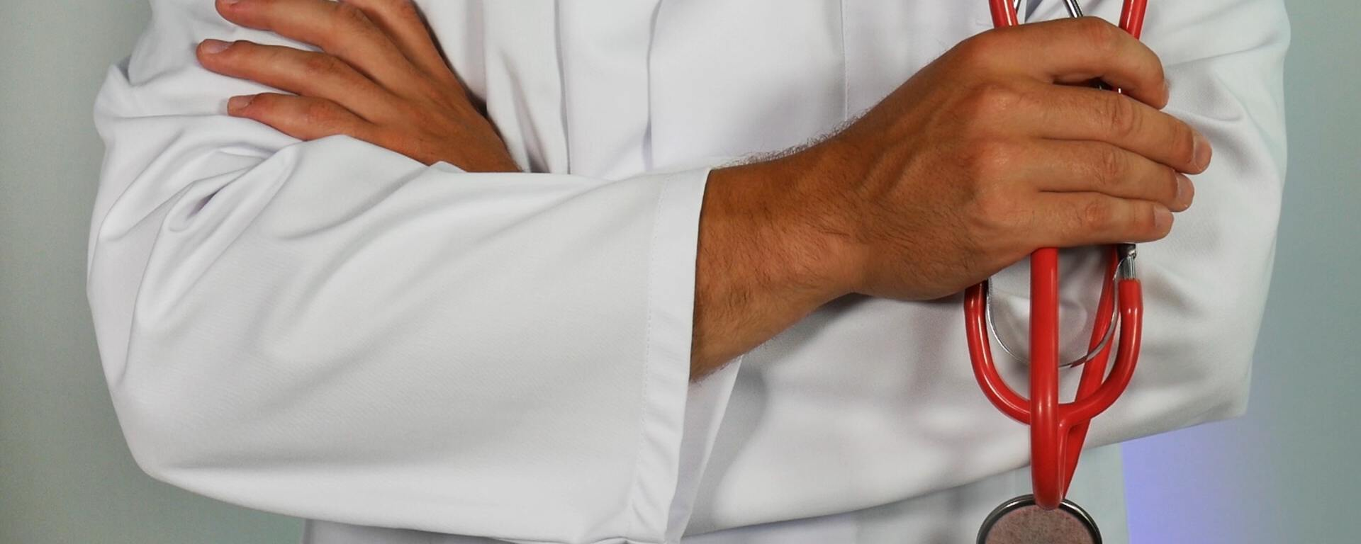 A man in a white lab coat is pictured waist down, holding a stethoscope