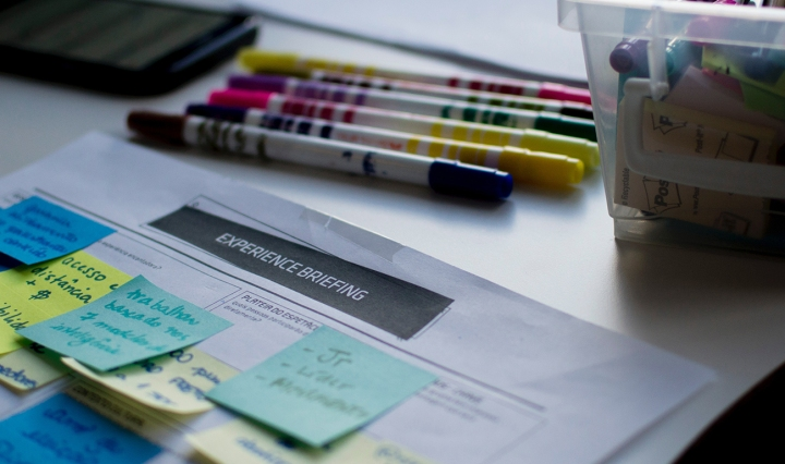 A piece of paper with lots of bright sticky notes,pens and textas in the background