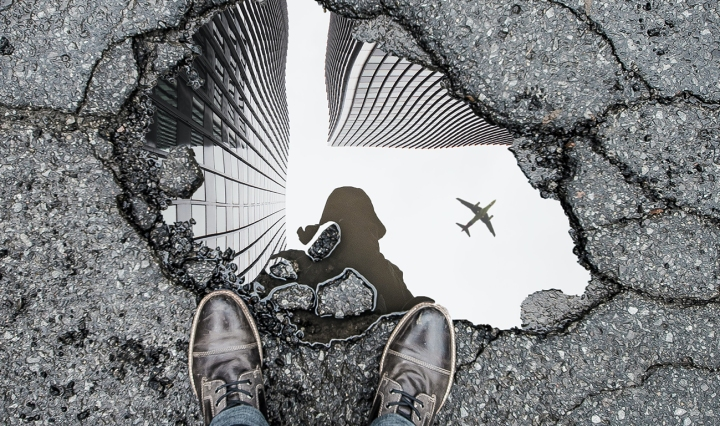 A person's shoes are shown from POV, standing over a puddle, where the person's outline is reflected