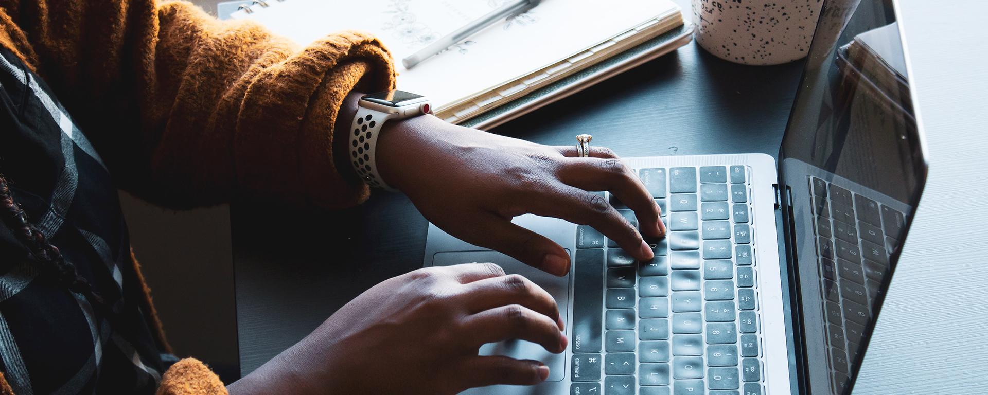 Close up of a Brown woman's hands as she types on her laptop
