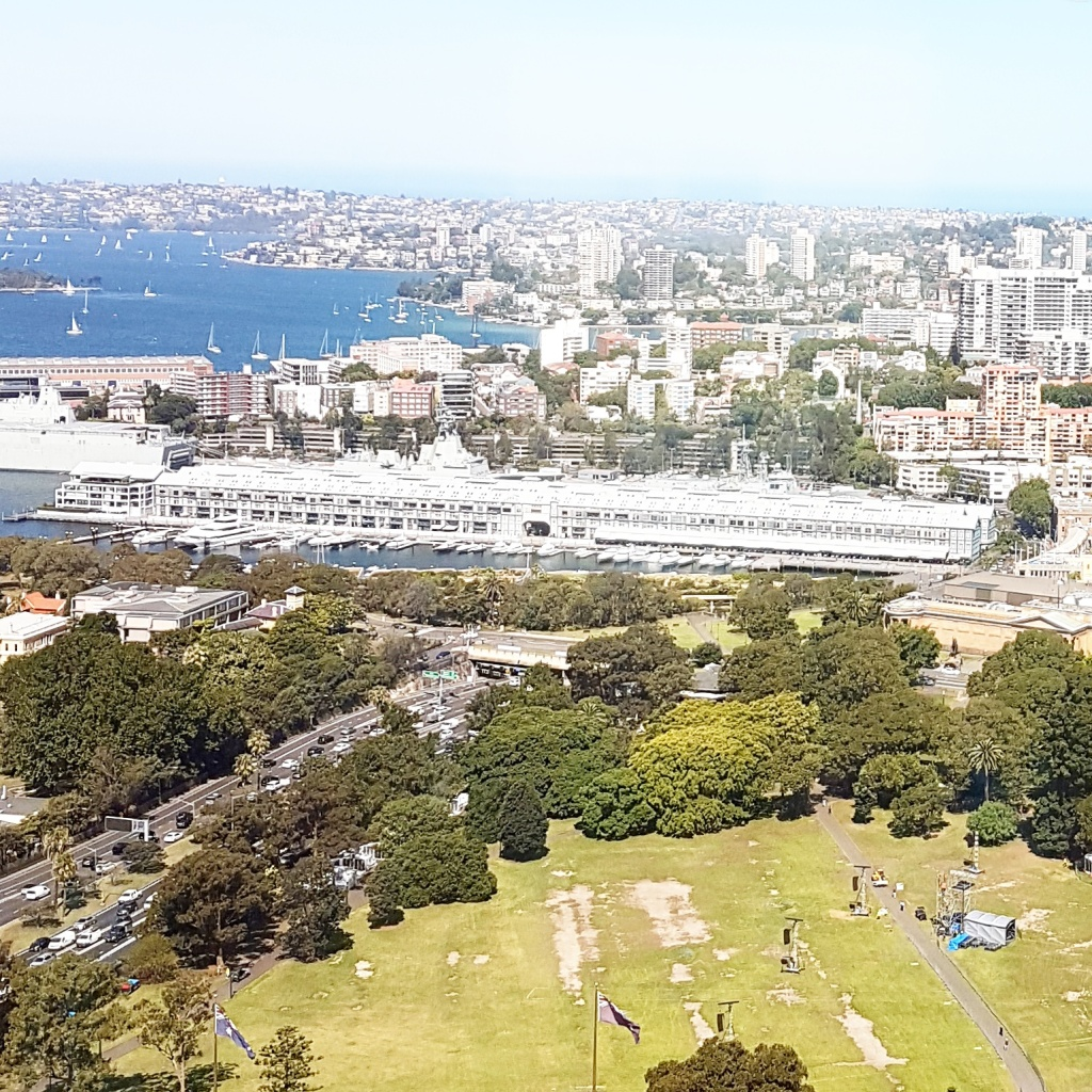 Aerial view of the Sydney CBD showing a park in the foreground, large buildings in the background and the shoreline with boats