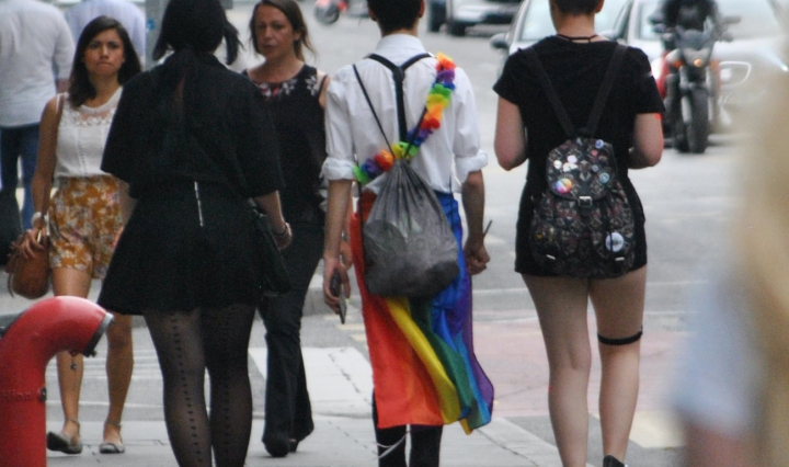Youth are seen walking from the crowd, from the back. One of them wears the pride flag