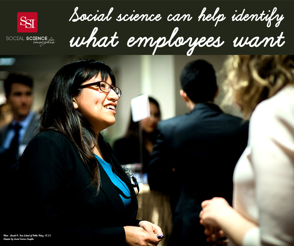 A Brown Latin woman with glasses talks to a white woman at an event. Ext: Social science can help identify what employees want