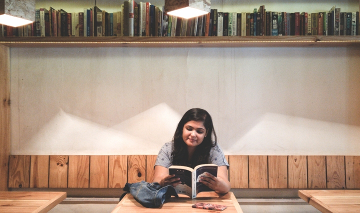 An Indian woman is reading in a library