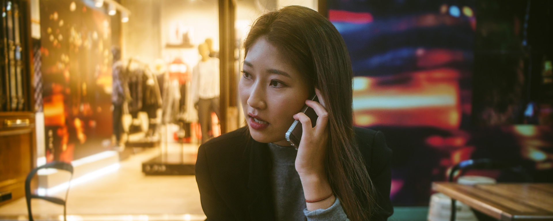 An Asian woman talks on the phone with a serious look on her face
